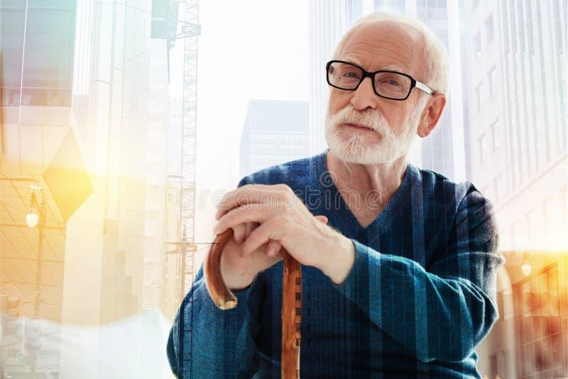 Pensionista pacífico que mira en la distancia mientras que se inclina en el bastón fotografía de archivo libre de regalías