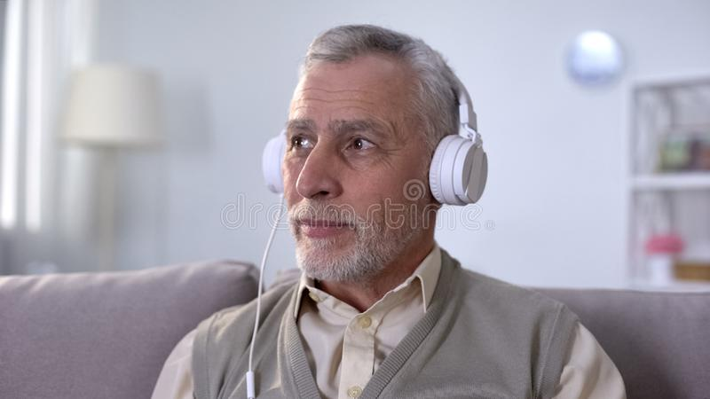 Pensionista positivo nos fones de ouvido que escuta a música, apreciando o rádio favorito imagens de stock