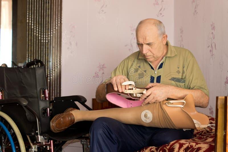 Pensionista que cabe su pierna artificial imágenes de archivo libres de regalías