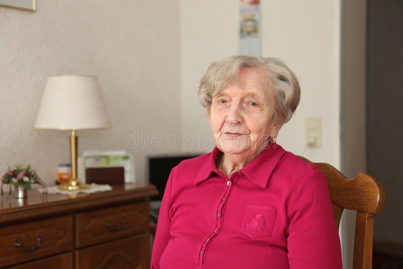 Pensionista que senta-se na cadeira na sala de visitas imagem de stock royalty free