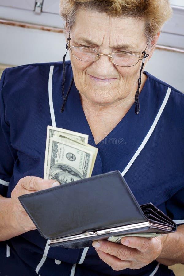 Pensionista que sostiene la cartera con el dinero imagen de archivo