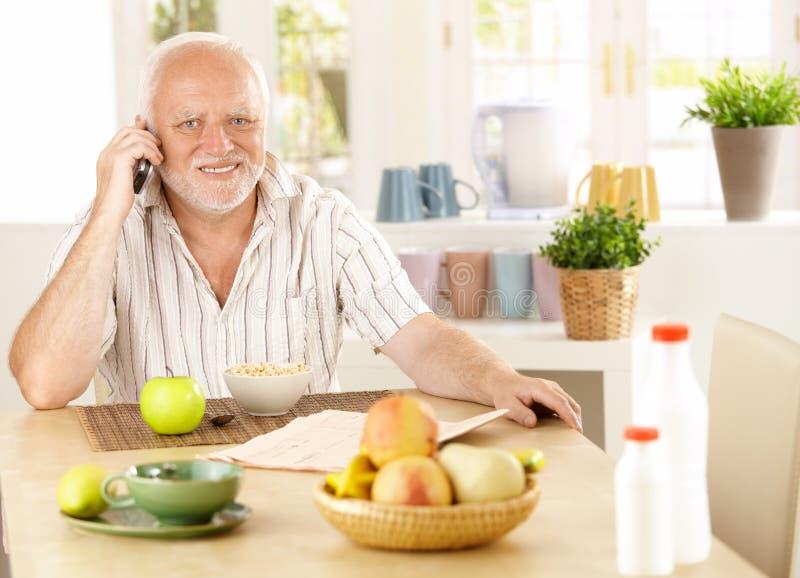 Pensionista sano que usa el teléfono celular en el desayuno foto de archivo libre de regalías