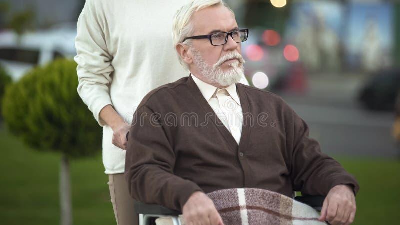 Pensionista triste en la silla de ruedas, cuidado que toma femenino viejo hombre discapacitado, clínica de reposo fotografía de archivo libre de regalías
