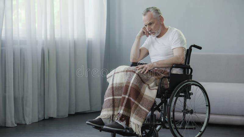 Pensionista triste que se sienta en silla de ruedas y que espera a su familia en la clínica de reposo imágenes de archivo libres de regalías