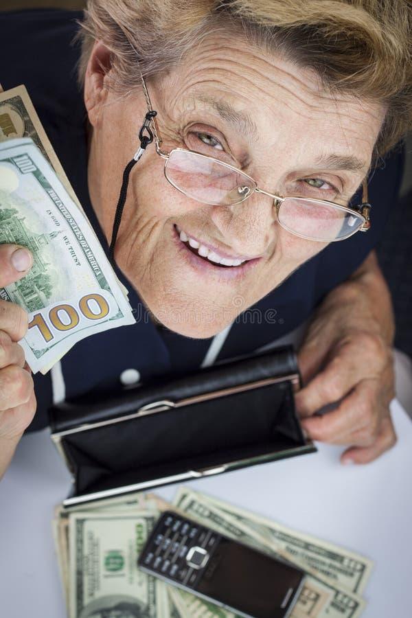 Pensionista y dinero de la mujer fotografía de archivo