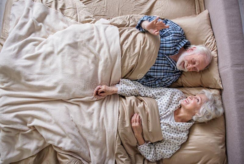 Pensionistas felices que mienten en cama imagen de archivo