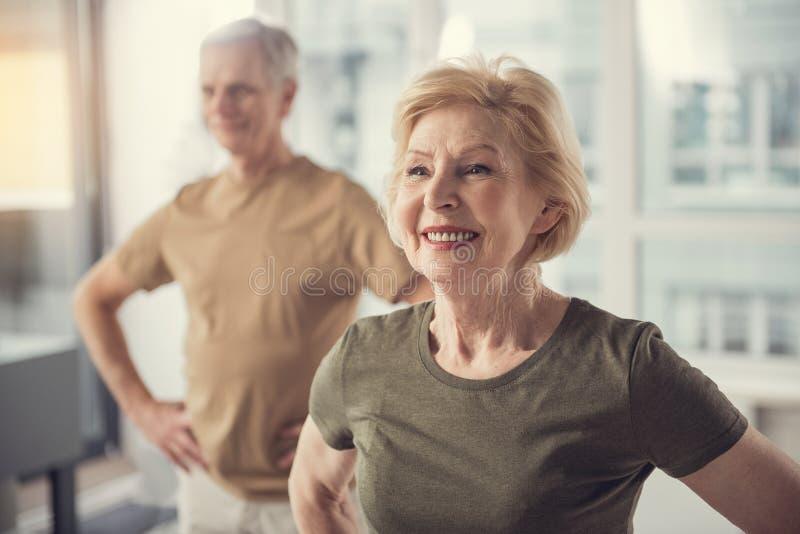 Pensionistas positivos que hacen ejercicios físicos dentro fotografía de archivo