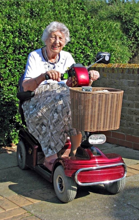 Pensionné expliquant le scooter de mobilité images stock