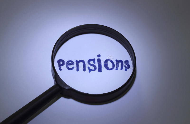 Pensions. Inscription word magnified under a magnifying glass royalty free stock photography