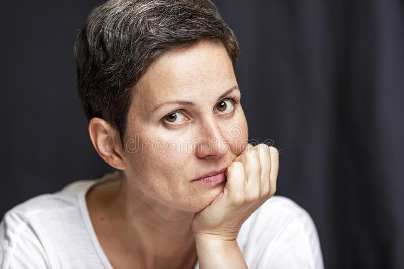 Pensive adult woman with short hair. Portrait on a black background. Close-up royalty free stock photography
