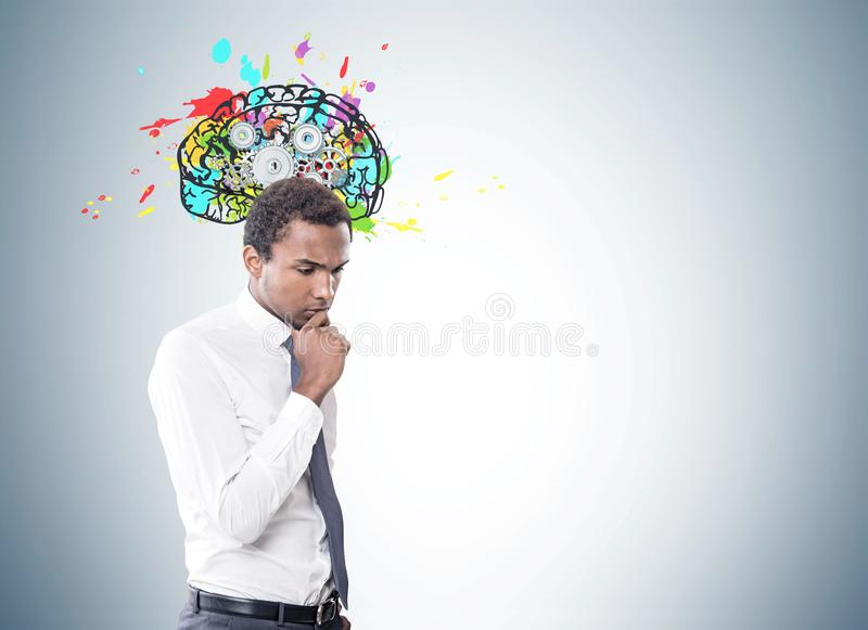 Pensive African American businessman, brain cogs. Portrait of a young pensive African American businessman wearing a white shirt and a gray tie. Gray wall stock images