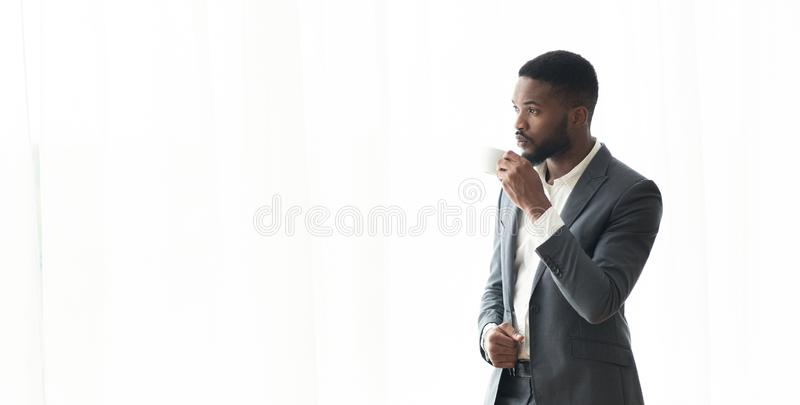 Pensive African American businessman enjoying cityview from window in office royalty free stock photography