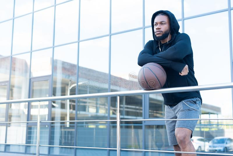 Pensive african american man in earphones leaning at railings with basketball ball. And looking away royalty free stock photo