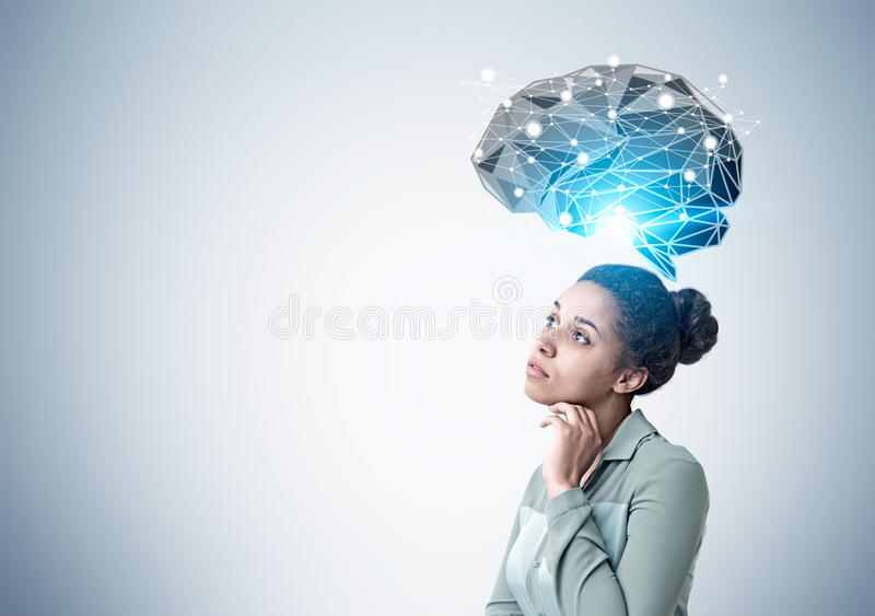 Pensive African American woman and brain hologram. Side view of a pensive African American woman standing near a gray wall with a black brain hologram shining stock photos