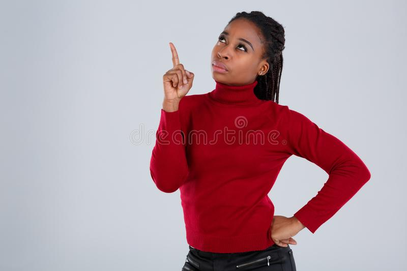 Pensive African American woman with a serious look looking up and showing the index finger up. royalty free stock images