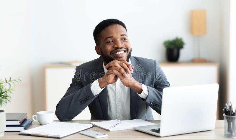 Pensive african businessman dreaming about something while working in office stock image