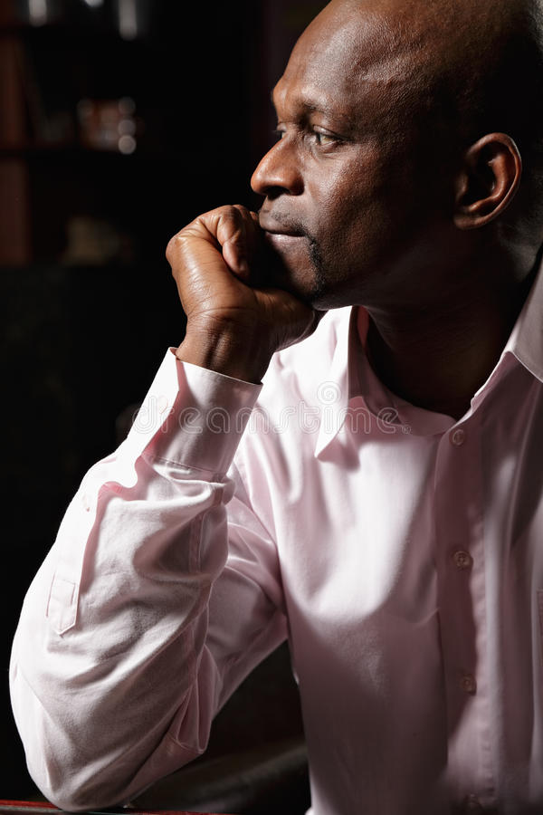 Pensive african man sideview royalty free stock photography