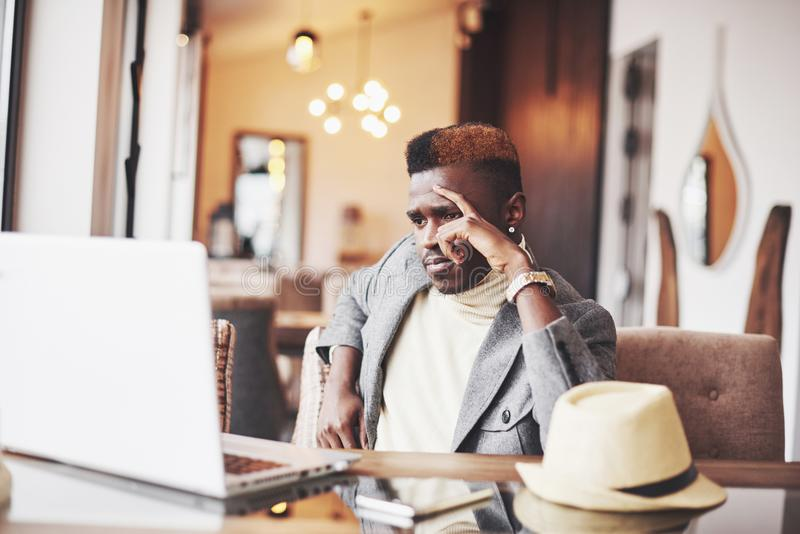 Pensive afro american handsome professional writer of popular articles in blog dressed in trendy outfit and glasses royalty free stock photos