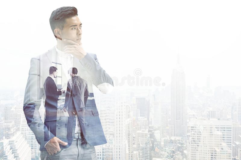 Pensive Asian businessman in a foggy city. Pensive young Asian businessman wearing a dark suit is thinking standing against a foggy city background. Mock up royalty free stock photos