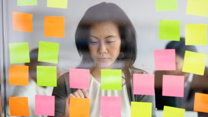 Pensive Asian businesswoman brainstorm develop business project on notes. Thoughtful middle-aged Asian businesswoman write ideas on colorful notes on glass stock photo