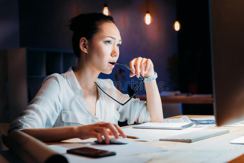 Pensive asian businesswoman holding eyeglasses and looking at computer monitor stock photos
