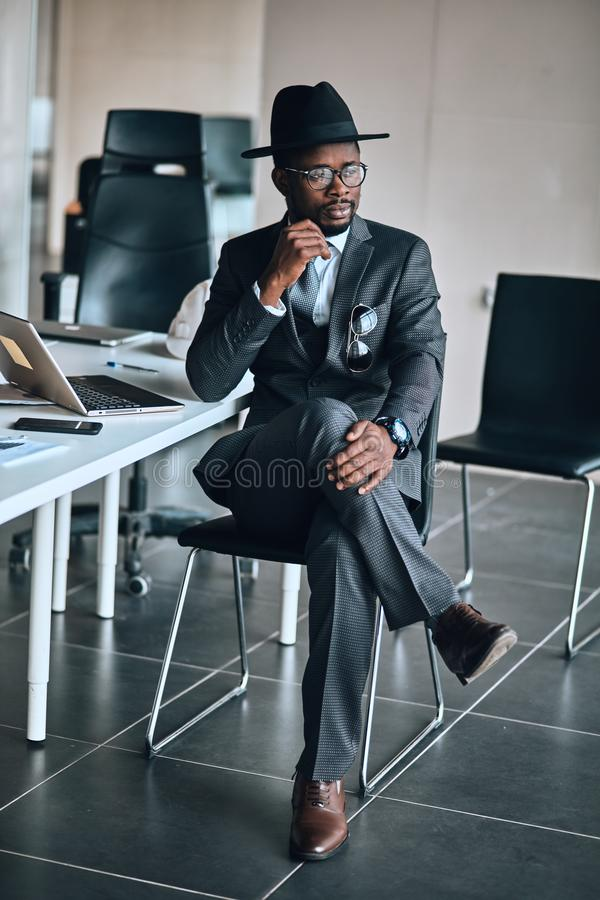 Pensive awesome man is sitting with crossed legs indoors royalty free stock photo