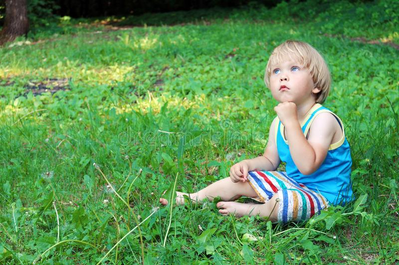 Pensive baby boy sitting on green grass, Dreamer stock photo
