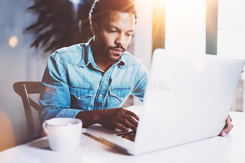 Pensive bearded African working at home while sitting the wooden table.Using modern laptop for new job search.Concept of stock photos