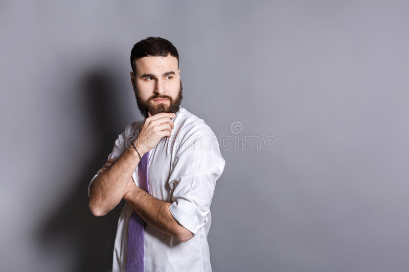 Pensive bearded businessman with hand on chin royalty free stock photography