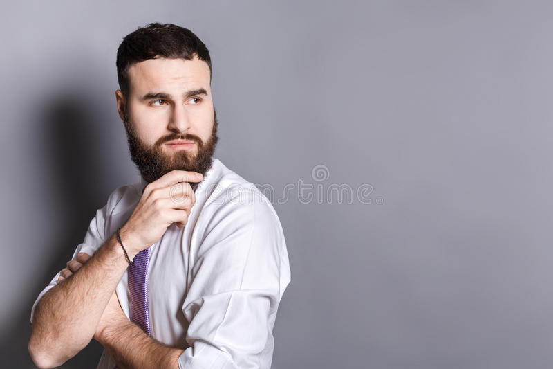 Pensive bearded businessman with hand on chin stock photo