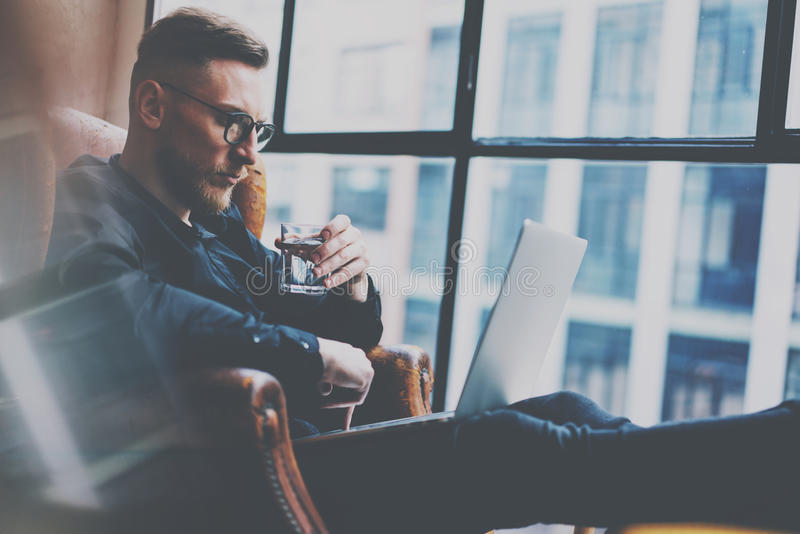 Pensive bearded businessman working at the modern loft office.Man sitting in vintage chair,holding in hands glass of royalty free stock photo