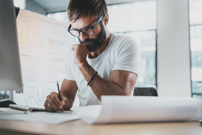 Pensive bearded designer wearing eye glasses and white tshirt, working at modern loft studio-office.Man drawing scetches royalty free stock photos