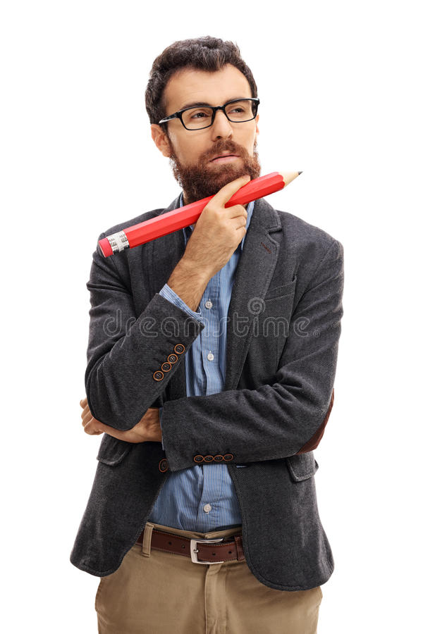 Pensive bearded guy holding a big pencil royalty free stock images