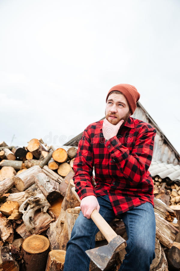 Pensive bearded man with axe sitting on logs and thinking royalty free stock images