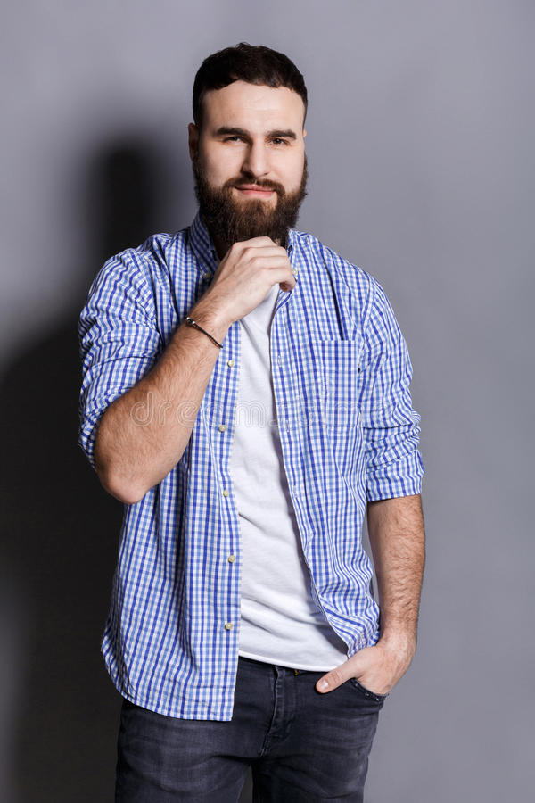 Pensive bearded man posing with hand on chin stock images
