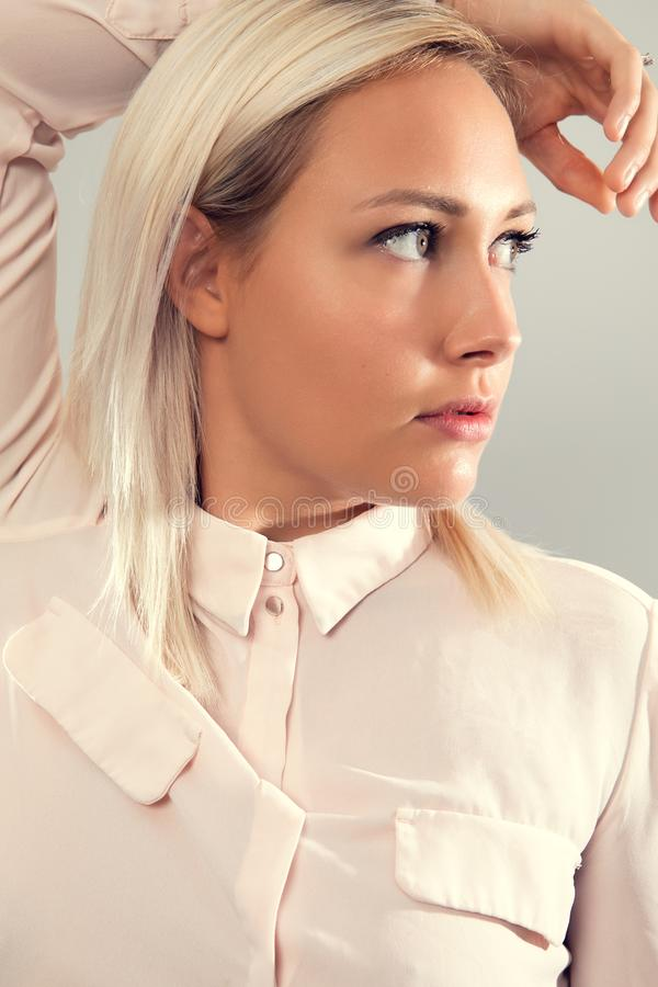 Pensive beautiful female blonde model in shirt looking away from camera royalty free stock photo