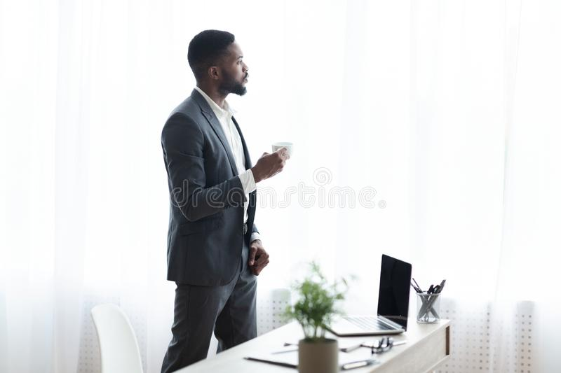 Pensive businessman standing near window in office and drinking coffee stock images