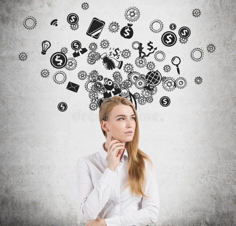 Pensive blond businesswoman, cogs and icons. Portrait of a young blond businesswoman wearing a white shirt and standing near a concrete wall with gears and stock photo