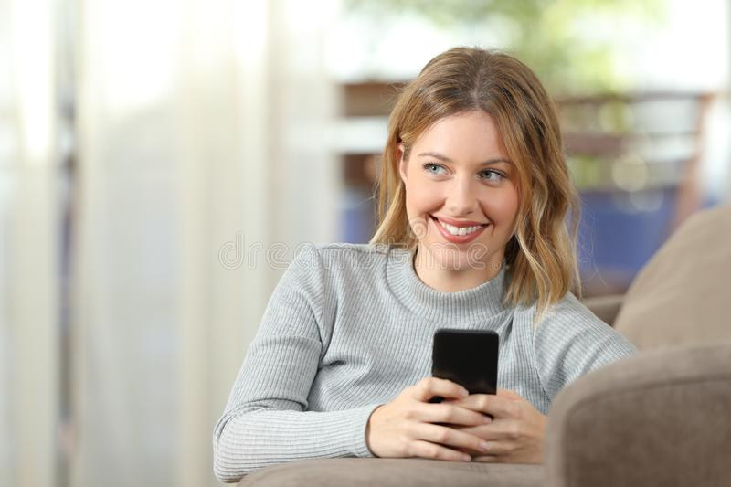 Pensive blonde using a smart phone at home royalty free stock images
