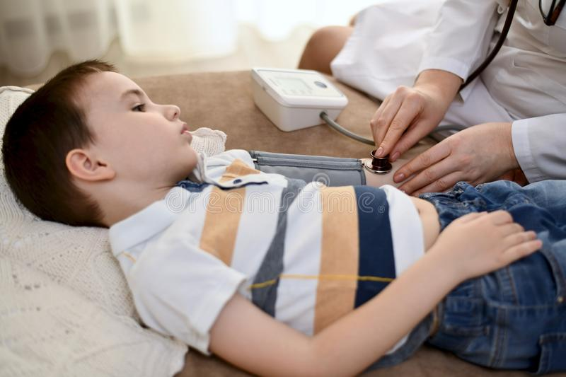 The doctor measures the pressure of the boy. royalty free stock photo