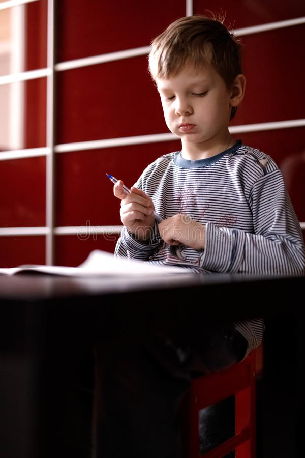 Pensive boy in a red chair at the table stock images