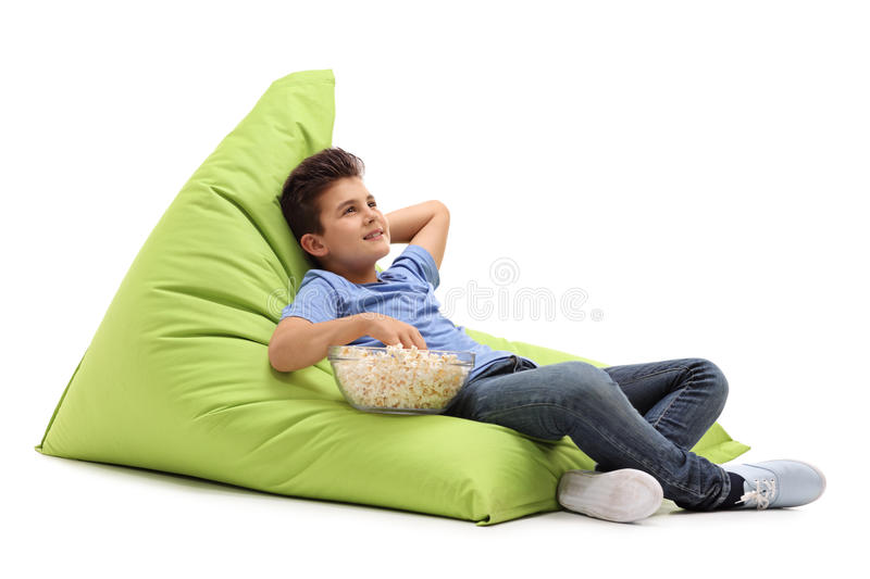 Pensive boy sitting on a beanbag royalty free stock images