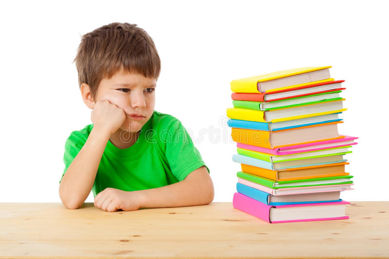 Pensive boy with stack of books royalty free stock images