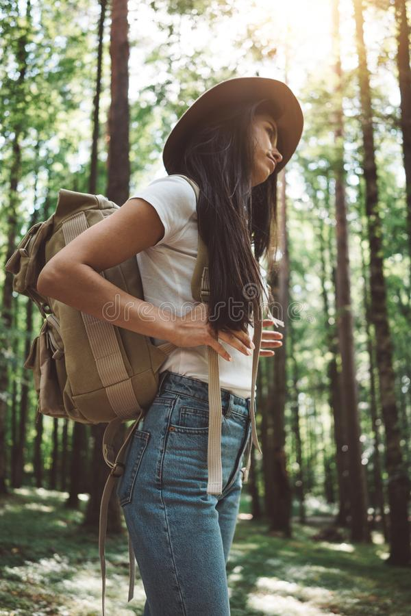 Pensive brave woman with backpack traveling alone among trees on outdoors. Young traveler girl hiking in forest stock photography