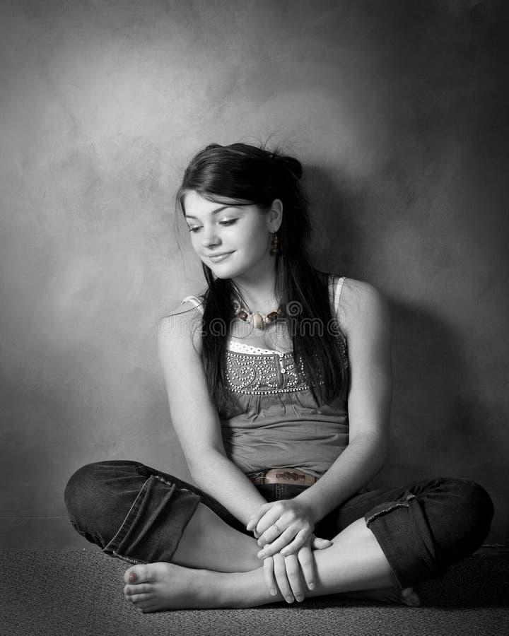 Pensive brunette. Portrait of teenage girl sitting cross-legged on floor stock photos