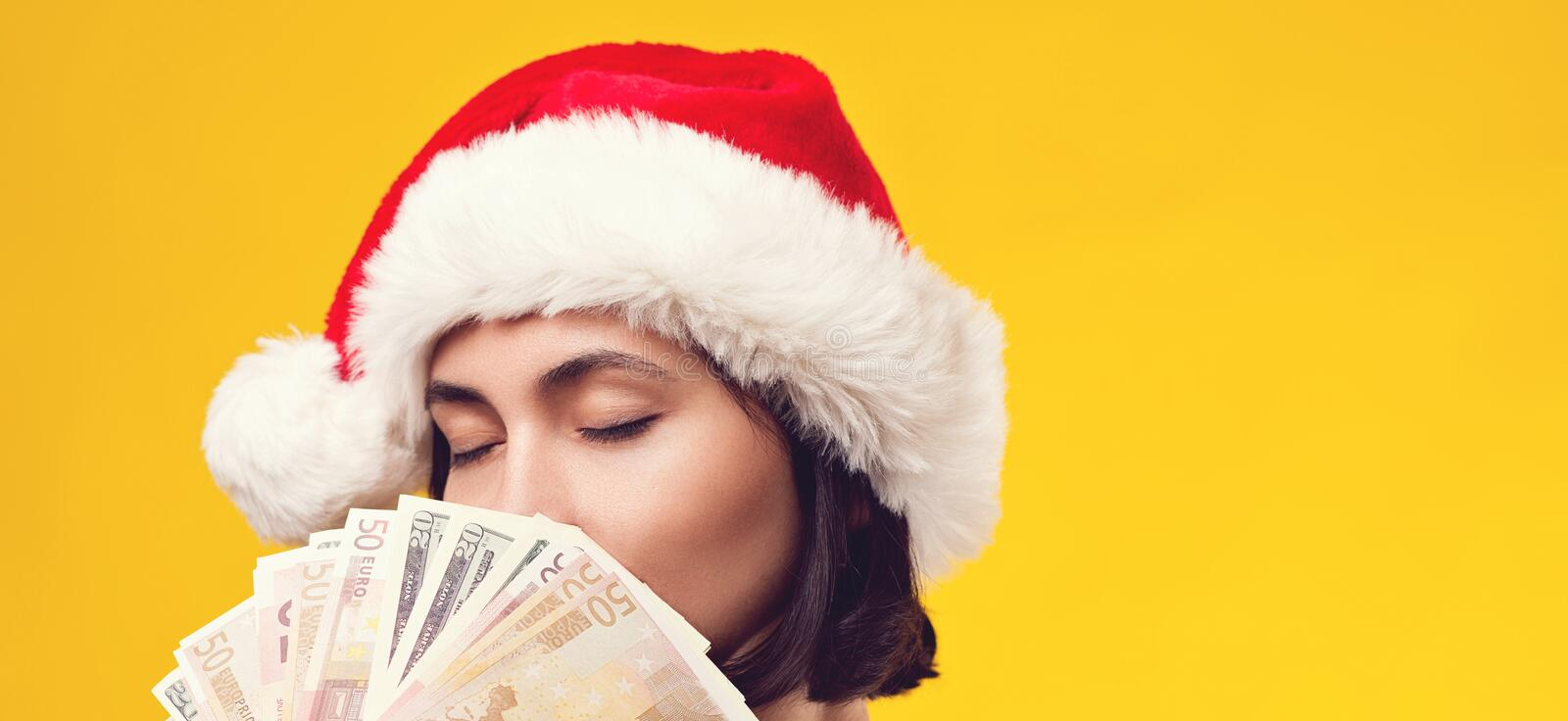 Pensive brunette woman in christmas hat holding money. Girl dreaming in Christmas. Isolated on yellow background, copy space. royalty free stock images