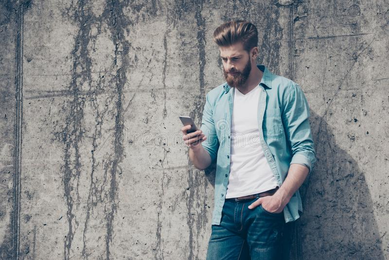 Pensive brutal young red bearded guy is typing a message outdoor stock photo