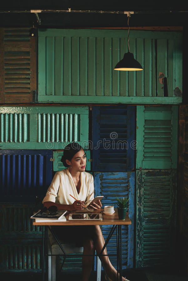 Pensive business lady. Beautiful Vietnamese business woman pondering over new ideas and taking notes when sitting in atmospheric cafe royalty free stock images