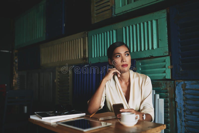 Pensive business lady. Pretty pensive Vietnamese business lady sitting at cafe table royalty free stock photos