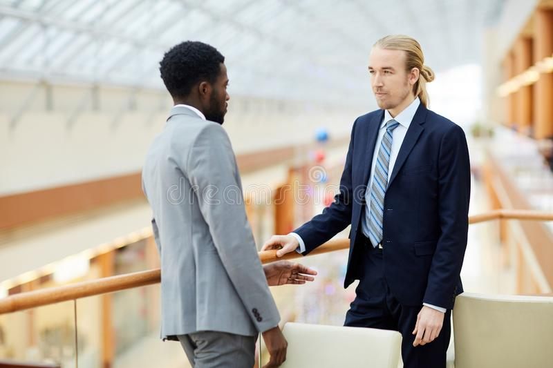 Pensive business partners talking in lobby royalty free stock photo